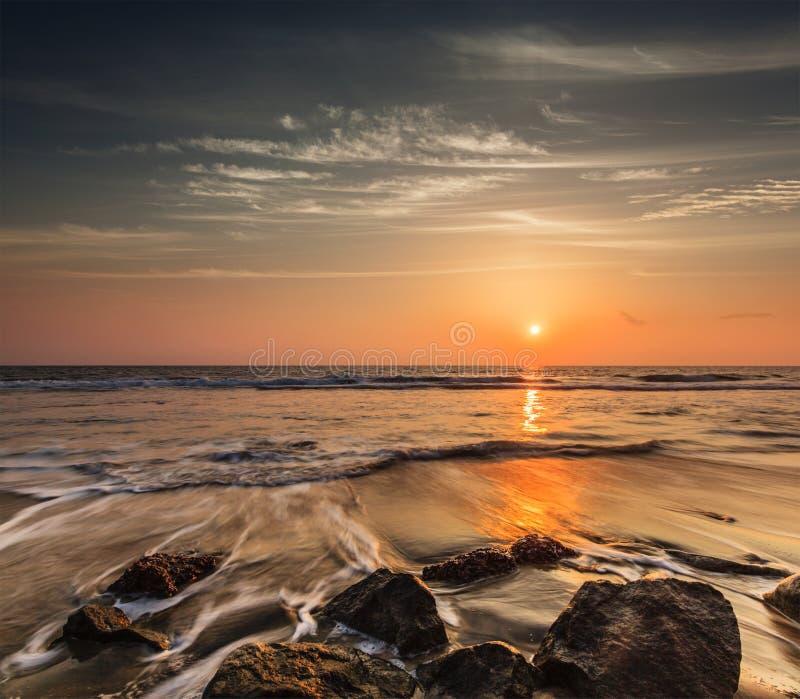 波浪和岩石在日落海滩  免版税库存照片