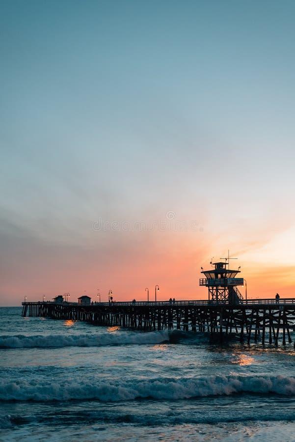 波浪在太平洋和在日落的码头在圣克莱芒特,橙县,加利福尼亚 免版税图库摄影
