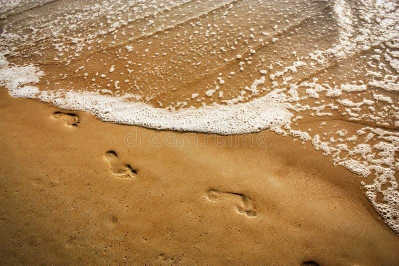 波浪盖在海滩的脚步 免版税图库摄影