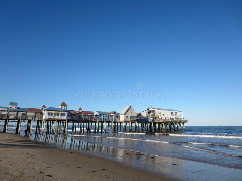 波浪舔历史的老果树园海滩码头 库存图片