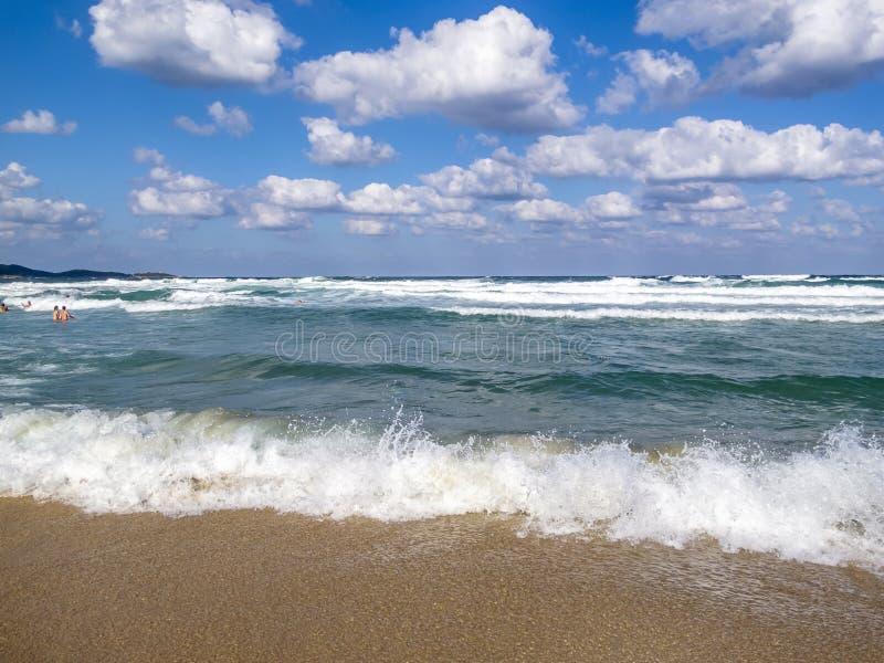 波浪遇见一个含沙黑海海滩,沐浴人在水距离 图库摄影