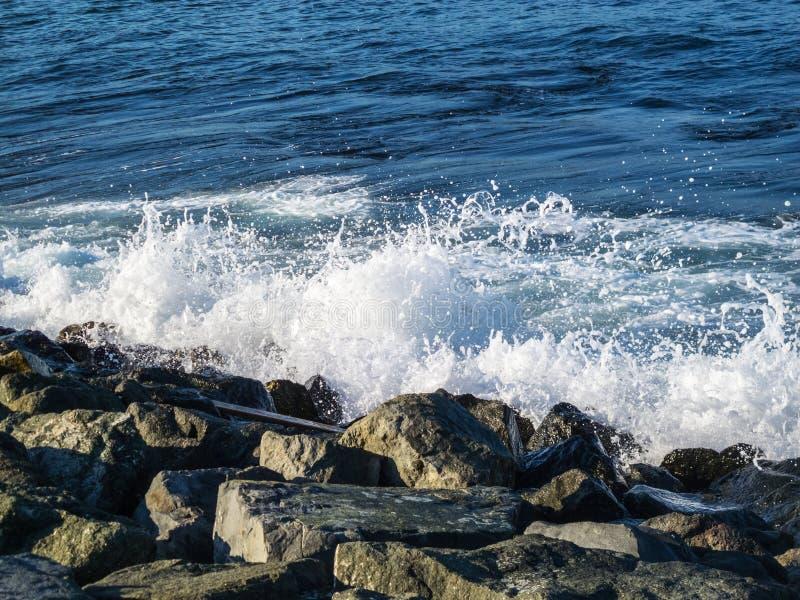波浪遇见防堤石头 免版税库存照片