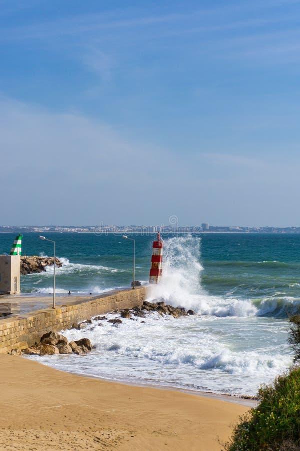 波浪飞溅反对灯塔在拉各斯,葡萄牙 库存照片