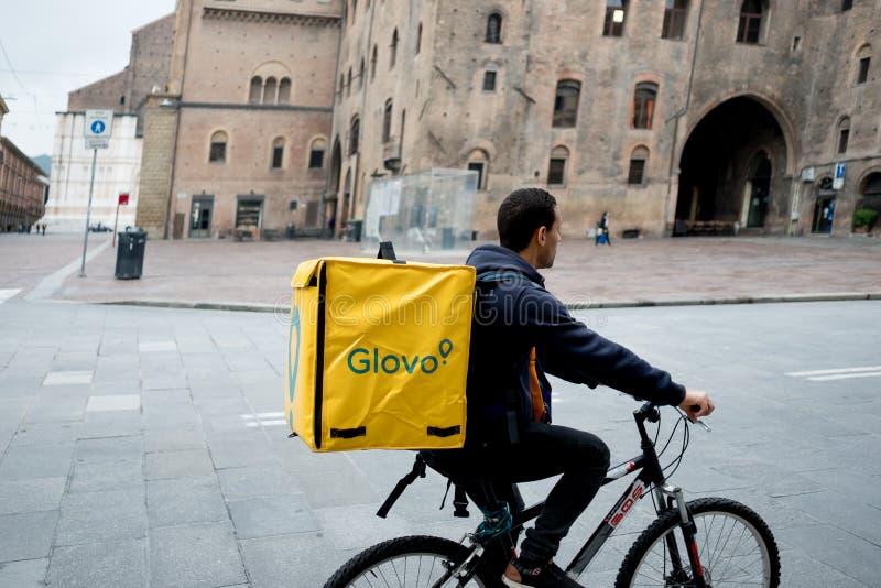 波隆纳,意大利- 2019年4月13日:做交付的年轻glovo车手在他的运转在用意大利人的所谓的违规记录经济的自行车 免版税库存照片