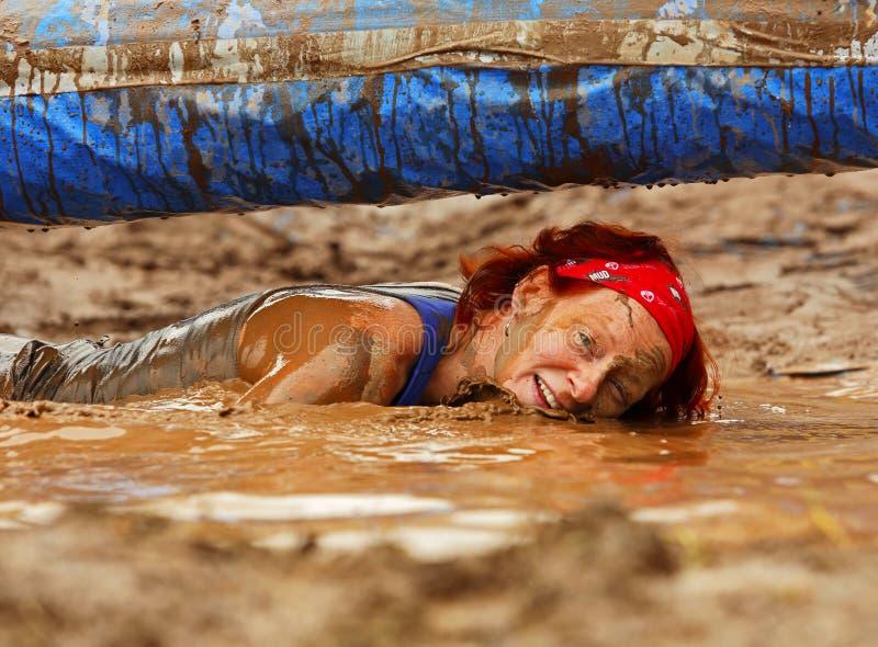 泥奔跑湿水的妇女 库存图片