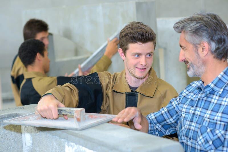 泥工和他的学生 免版税库存图片
