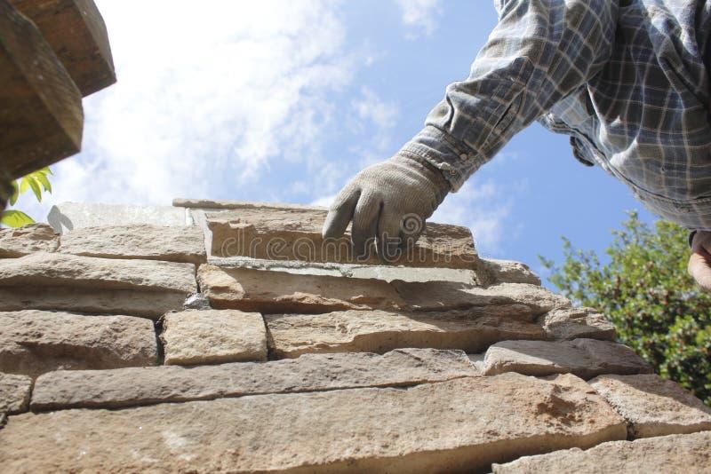泥工或瓦工设置石头或砖 免版税库存图片