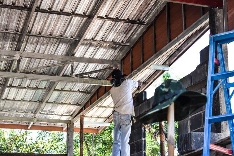 泥工或砖建造者在建造场所修筑水泥砖墙 工作者修建大厦或大厦housi的 库存图片
