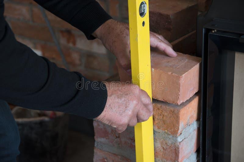 泥工检查墙壁的一块砖有在工地工作的一个水平仪的 免版税库存图片