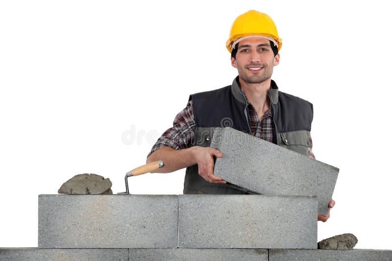 泥工运载的砖 免版税库存图片