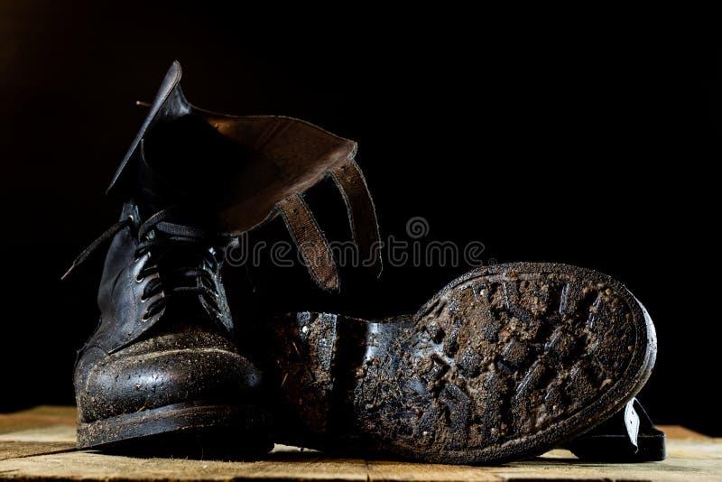 泥泞的老军事起动 黑颜色,肮脏的鞋底 木的表 免版税库存照片