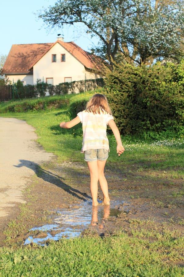 泥泞的水坑的小女孩 免版税库存照片