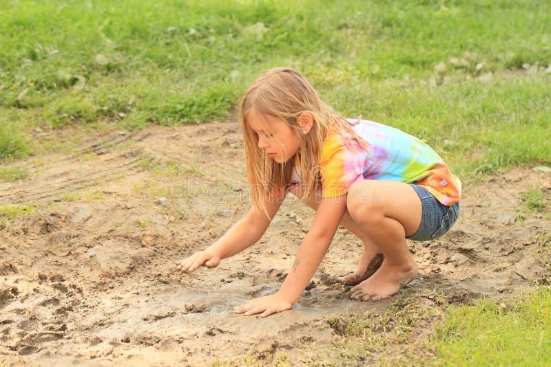 泥泞的水坑的小女孩 库存照片