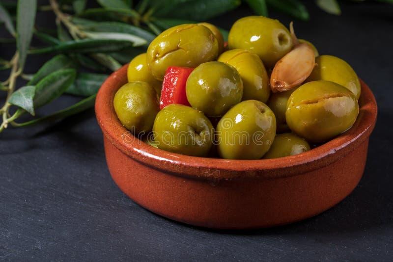 泥罐用在额外处女橄榄油、醋、香料用红辣椒和大蒜保存的工匠橄榄 免版税库存图片