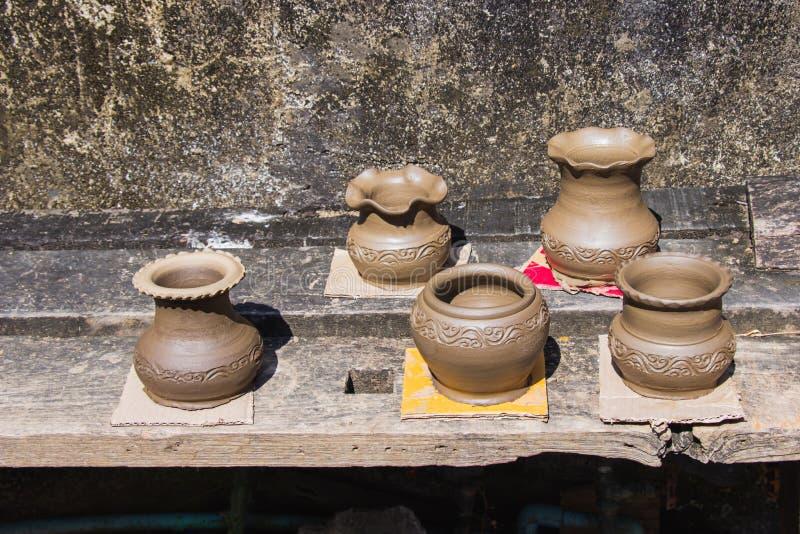 泥罐用手做了在室外安置的泰国传统瓷罐对村庄太阳在Ko Kret 库存图片