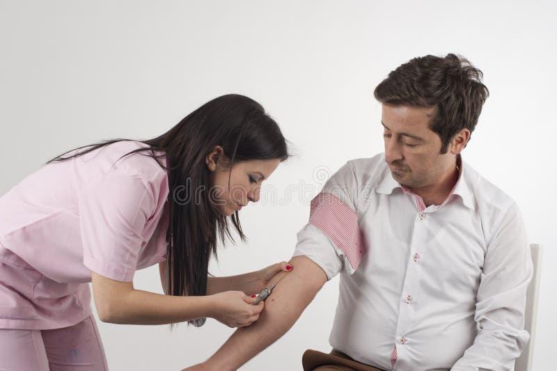 注射一个人的护士 免版税库存图片