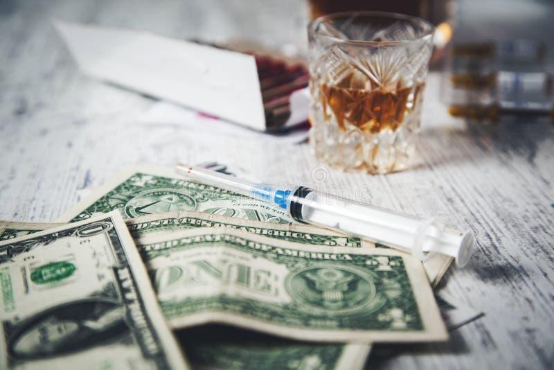 注射器和威士忌酒和金钱 免版税库存照片
