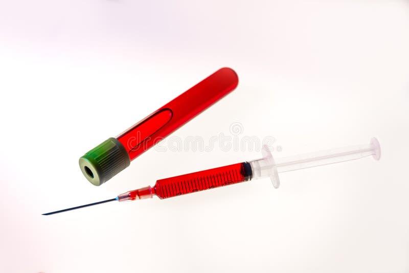 注射器和管有血液的在白色背景 免版税库存照片