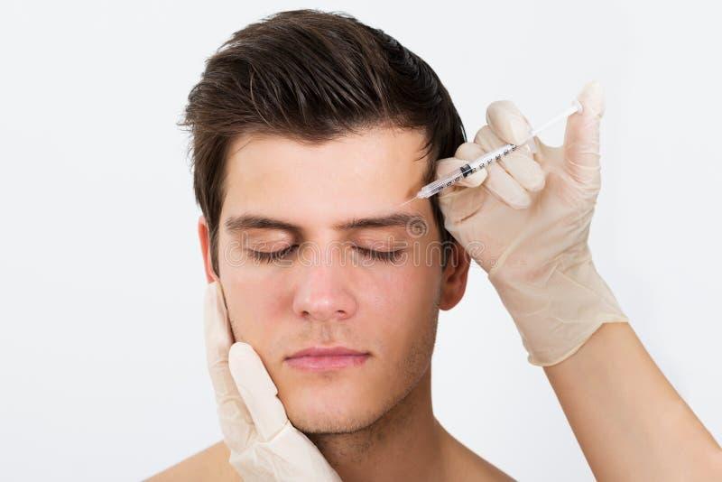注射有Botox的人手注射器 免版税库存图片