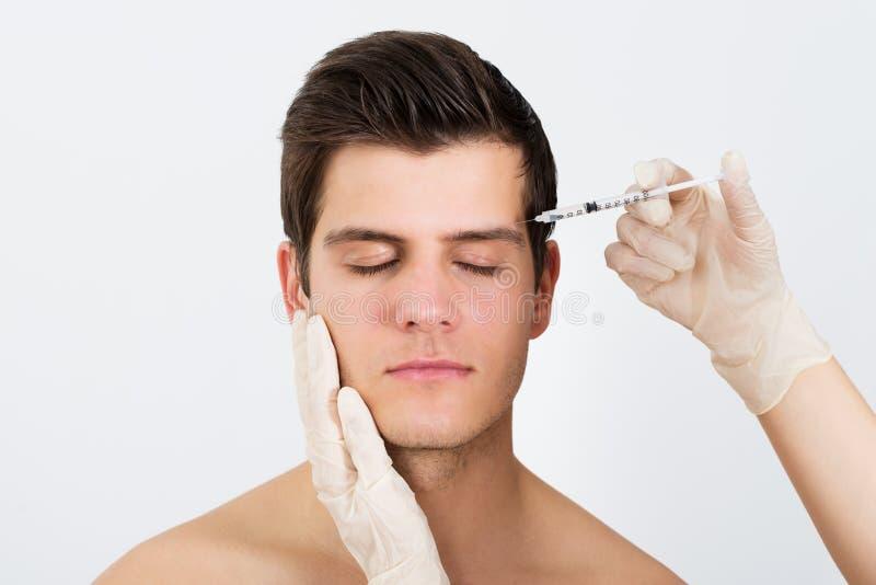 注射有Botox的人手注射器 免版税库存照片