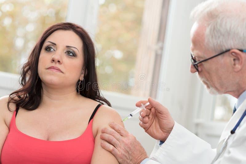 注射疫苗的医生对少妇 免版税图库摄影