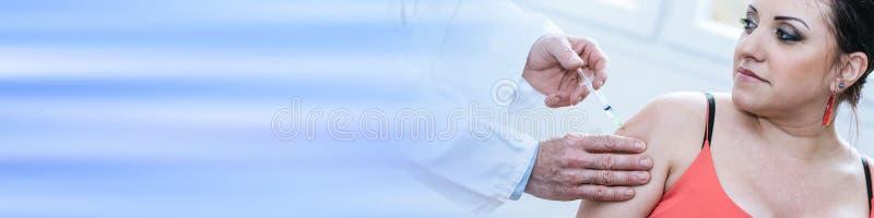 注射疫苗的医生对少妇 免版税库存照片