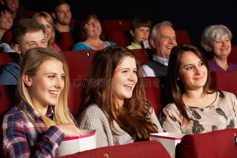注意在戏院的组十几岁的女孩影片 免版税库存图片