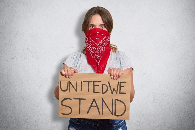 注意女权主义问题的果断年轻女人画象,相信平等权利,寻找支持,举行 免版税库存图片