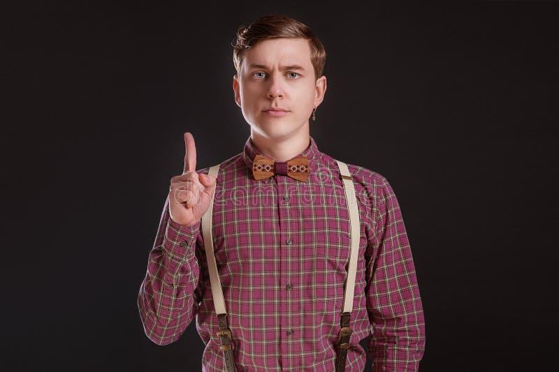 注意!葡萄酒衬衣保持手指被举和看照相机的蝶形领结的严密的英俊的年轻人,当站立反对时 免版税库存照片