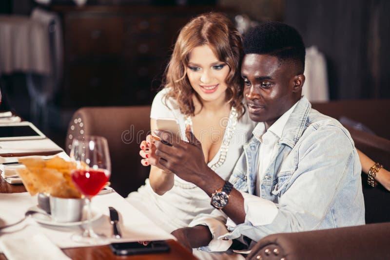 注意selfie waitng的混杂种族朋友晚餐,在餐馆 免版税库存图片