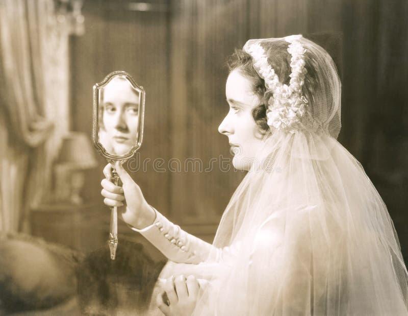 注视入手镜的新娘 免版税库存照片