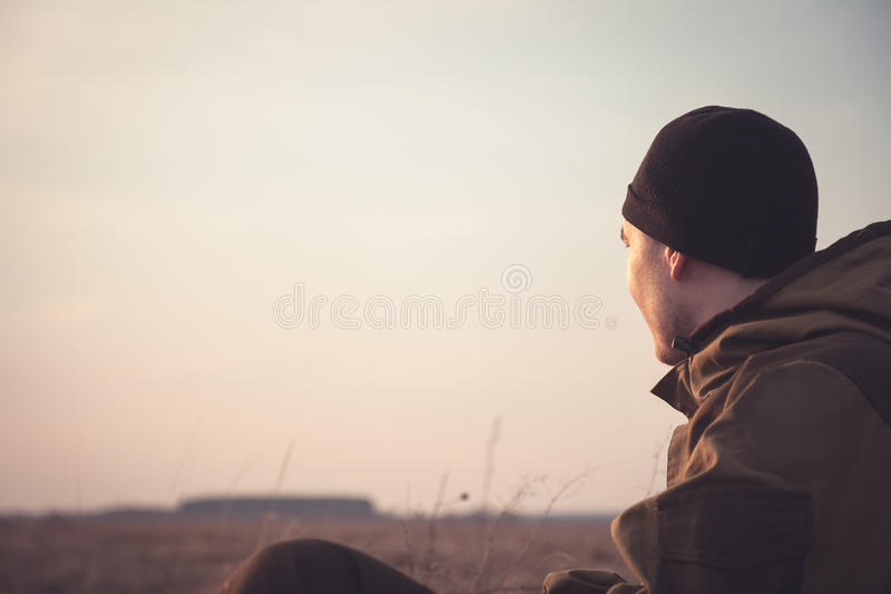 注视着入距离的年轻人在农村领域的黎明 光照亮他的面孔 免版税库存图片
