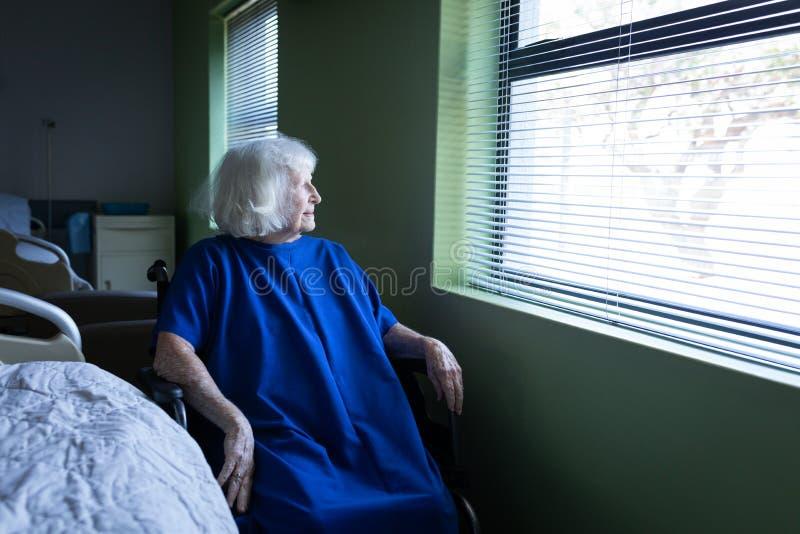 注视着外面通过窗口的资深女性患者医房 图库摄影