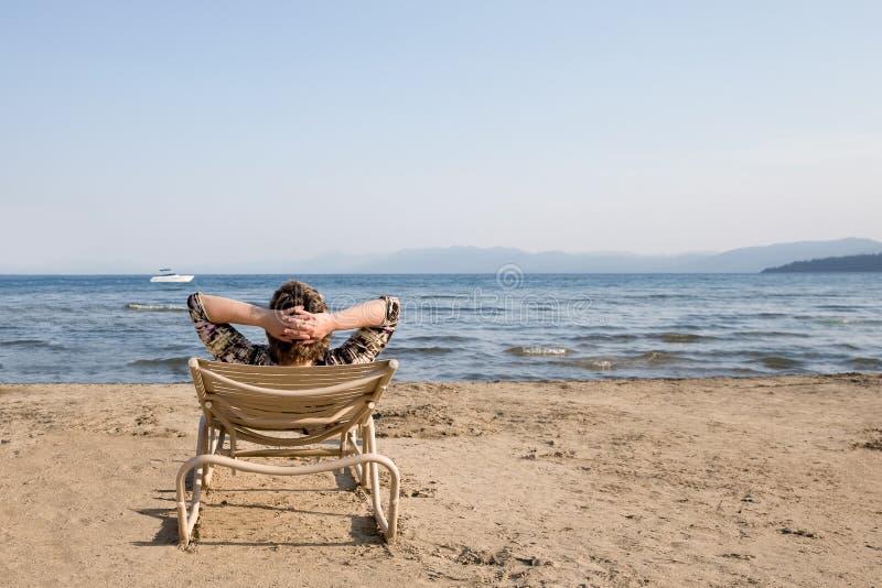 注视着天际的海滩睡椅的妇女 库存照片