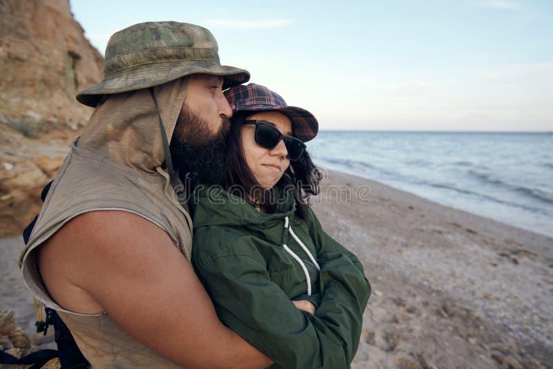 注视着对海滩天空的年轻浪漫旅客,享受日落海爱,夏天和旅行概念 库存照片