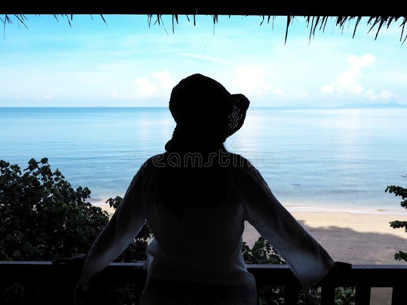 注视着对海的后面看法剪影妇女在海滩背景的手段 免版税库存图片