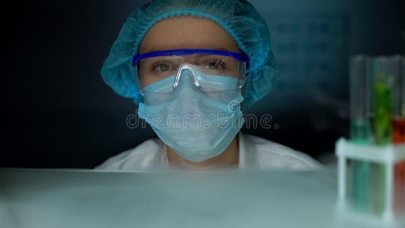 注视着对照相机的防护制服的科学家,专业工作场所 免版税库存图片
