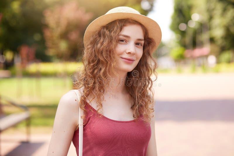 注视着直接地照相机、佩带的草帽和红顶的甜可爱的年轻女性室外射击,有在肩膀的袋子, 免版税库存照片