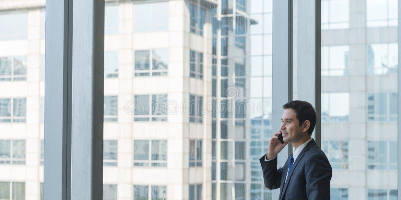 注视着看在大窗口外面下面城市的看法的成熟和确信的商业主管 图库摄影