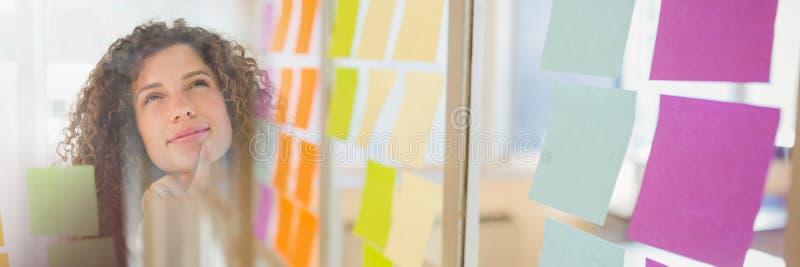 注视着稠粘的笔记和稠粘的笔记转折的妇女 免版税库存图片