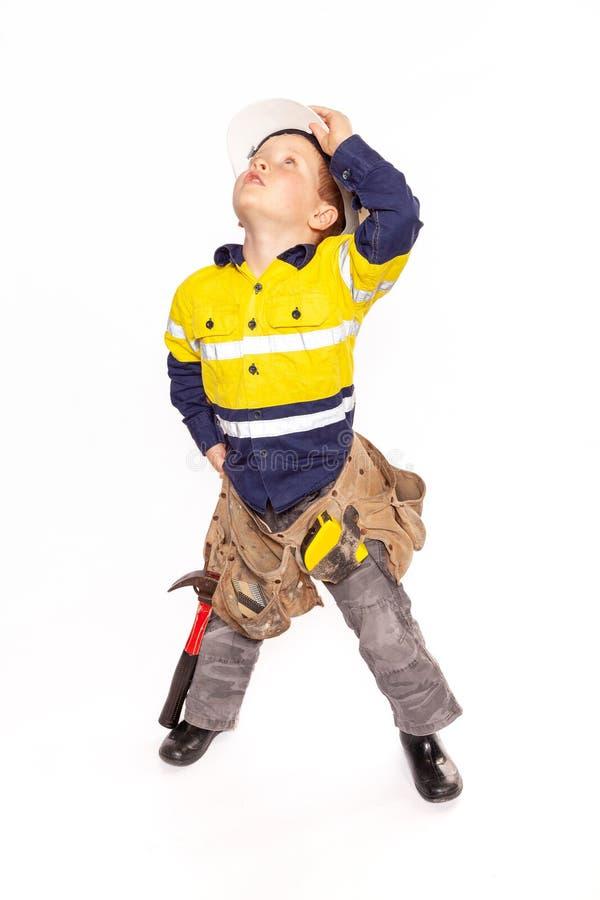 注视着进展,角色的喂即年轻白肤金发的白种人男孩使用作为建筑工人在一件黄色和蓝色衬衣 免版税库存图片