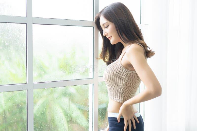 注视着通过与雨珠的玻璃窗的一名年轻快乐的亚裔妇女的画象她的家 生活方式和放松概念 免版税图库摄影