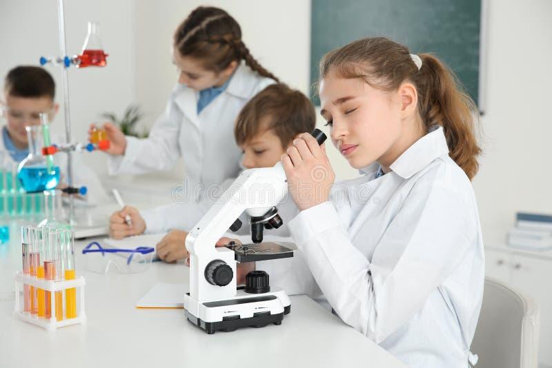 注视着通过显微镜和她的同学的聪明的女孩教训 图库摄影