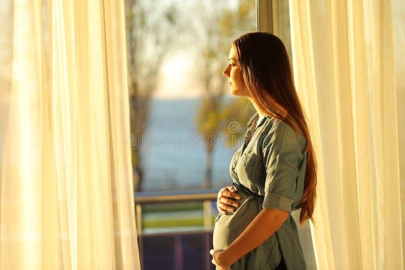 注视着通过窗口的孕妇日落 免版税库存图片