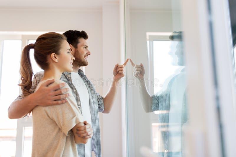注视着通过窗口的愉快的夫妇新的家 免版税库存照片
