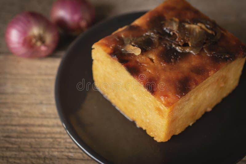 泰国乳蛋糕用在圈子黑色的盘子和青葱投入的绿豆在桌木头背景上把后侧方放 库存照片