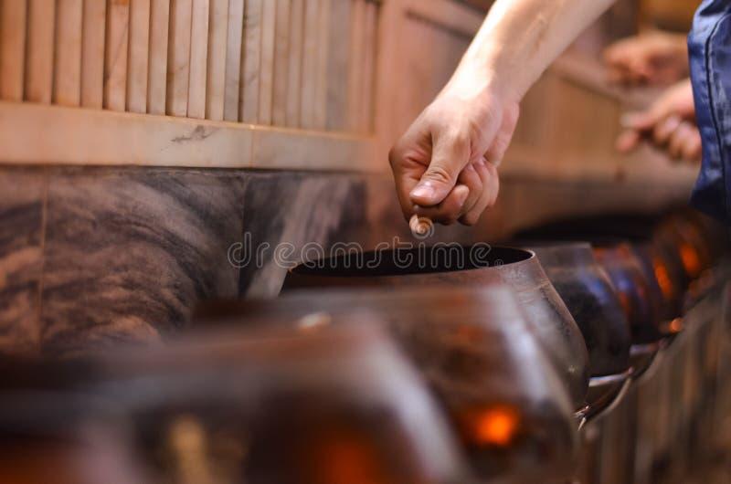 泰国传统捐赠通过投掷硬币对a 库存图片