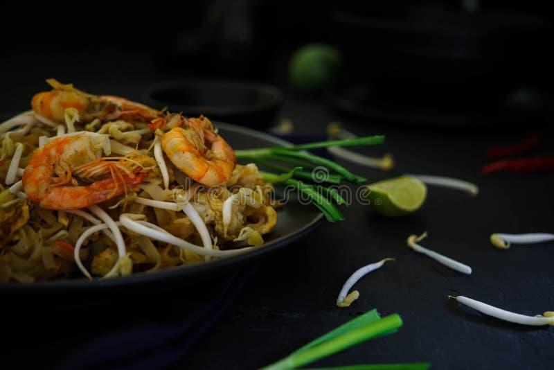 泰国传统烹调,填塞泰国,干面条、油煎的面条、虾和海鲜,街道食物,黑暗的食物摄影 库存照片