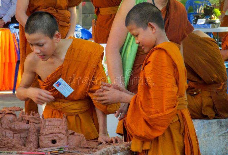 泰国做手工艺的寺庙wat的佛教年轻修士 免版税库存照片