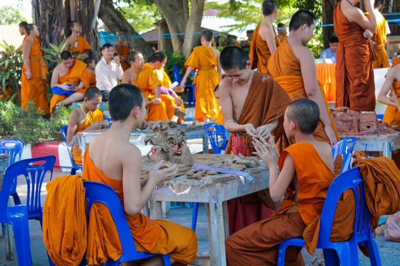 泰国做手工艺的寺庙wat的佛教年轻修士 免版税库存图片
